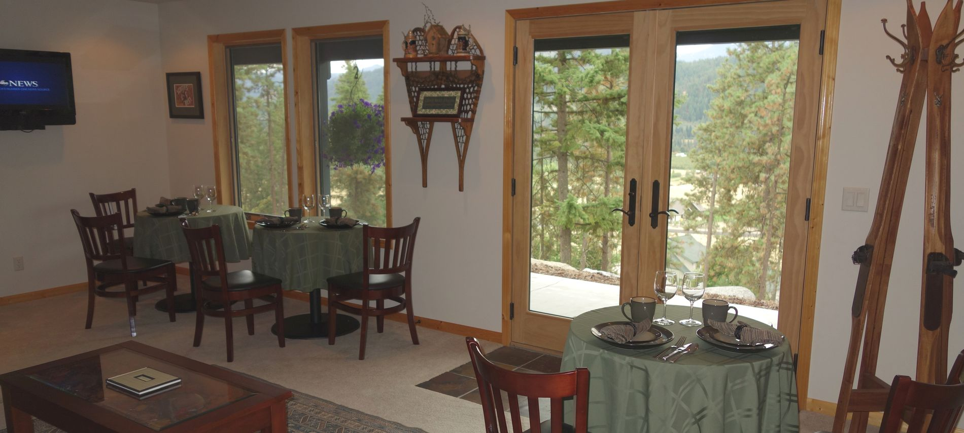 Interior of dining room showing exterior view of green trees and purple mountains.