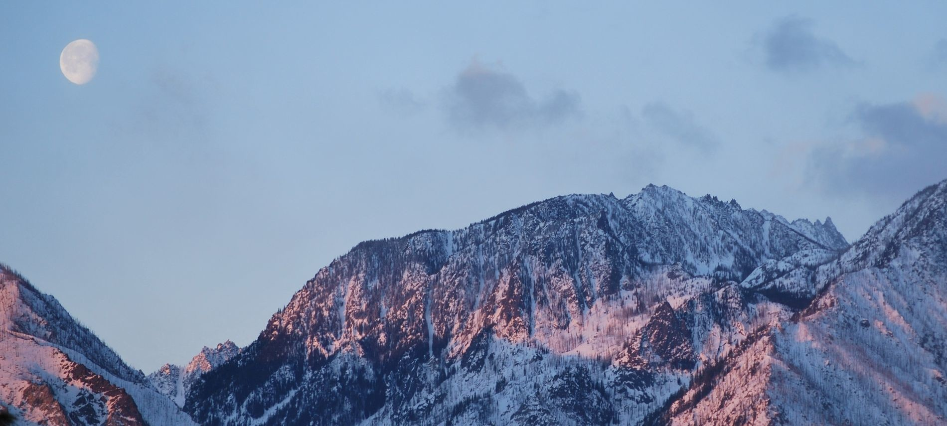Sunrise view of mountains with pink snow and a full moon setting.