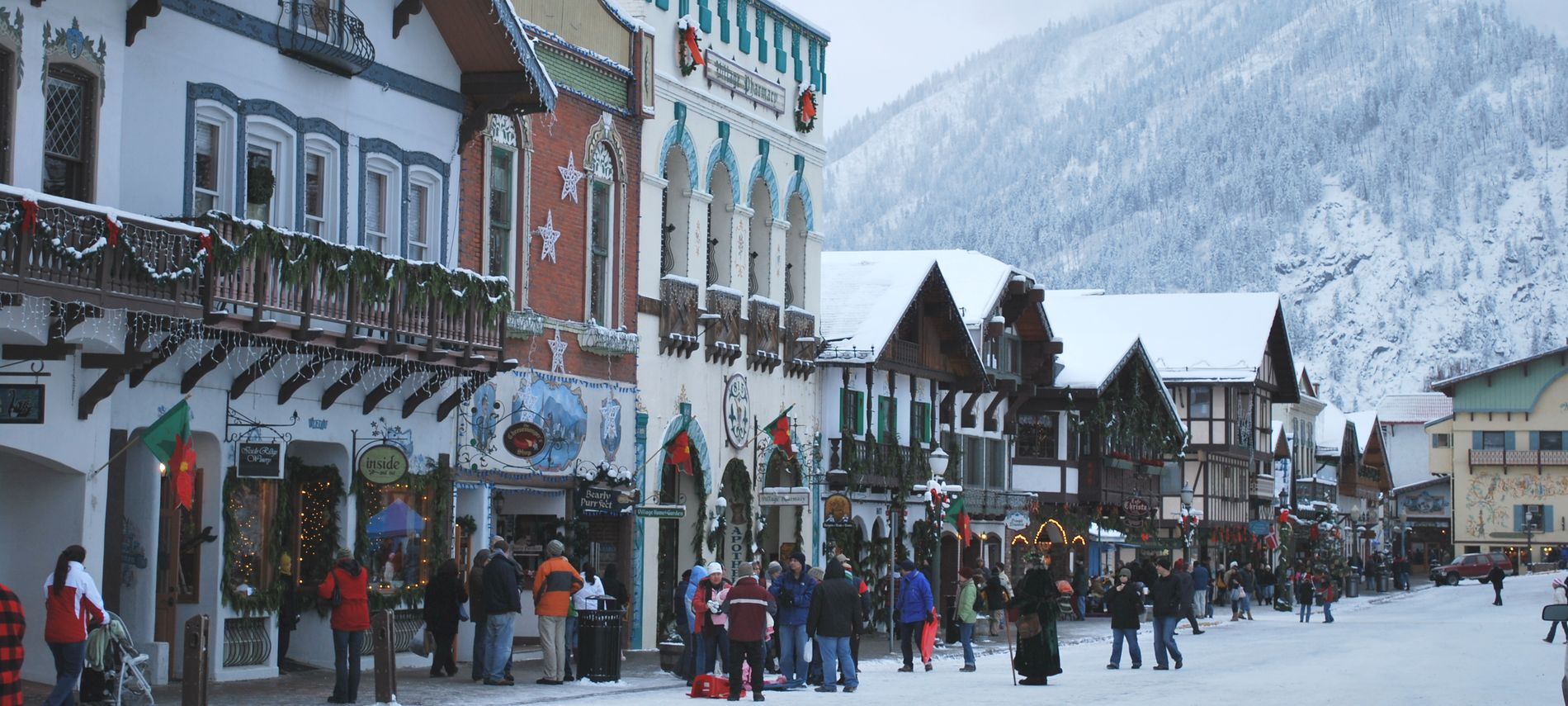 Exterior winter view of downtown Leavenworth showing white snow Christmas decorations.