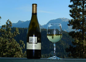 Exterior view of wine bottle and glass of wine set against blue mountains in background.