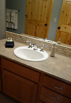 Interior view of bathroom showing sink, counter with stone backsplash and shower.
