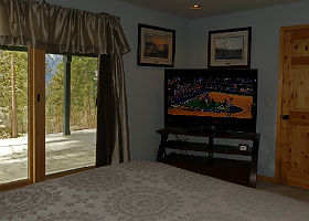 Interior view of room showing large HDTV, bed and sliding glass doors with view of mountains.