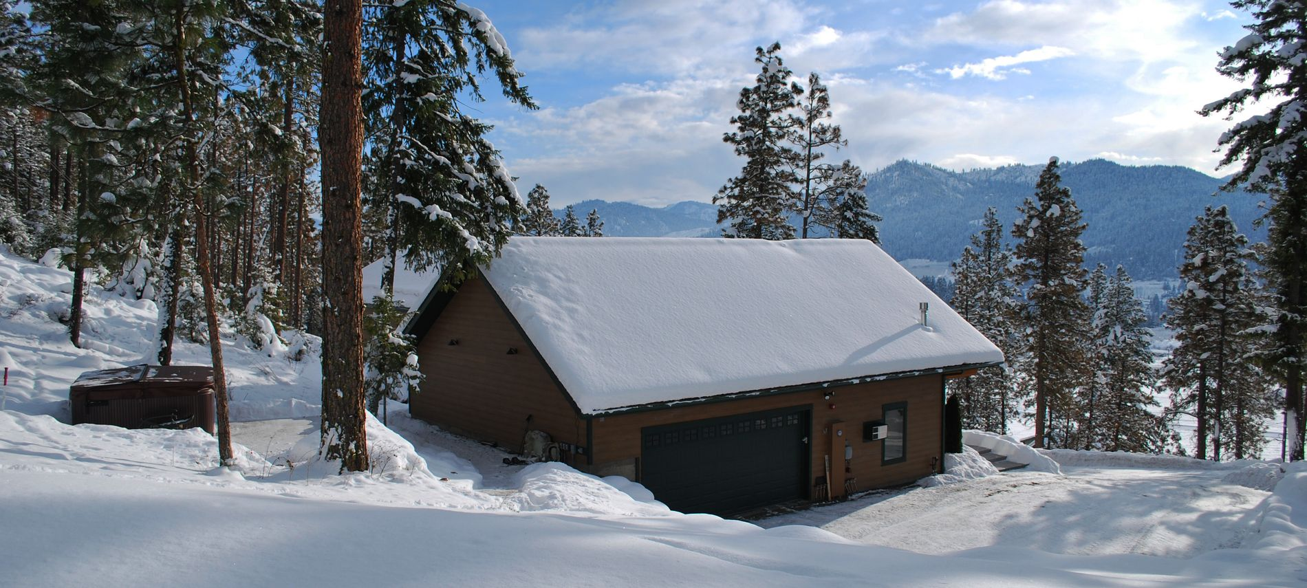 Exterior winter view of outdoor hot tub surrounded by white snow and dark blue mountains in the distance.
