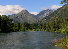 View of flowing river showing green mountains and blue water.
