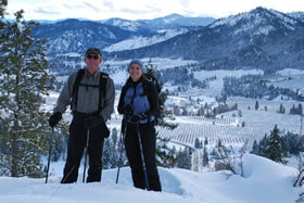 Exterior view of Innkeepers snowshoeing on a mountain top surrounded by white snow.